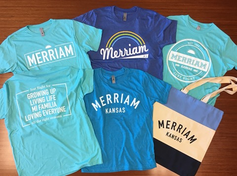 A variety of Merriam t-shirts in the colors of blue and aqua on a table.
