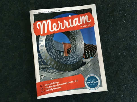 Cover of the 2021 Visitor Guide. Close up image of Bask (steel and words) sculpture with the title Merriam Kansas in white letters with red background.