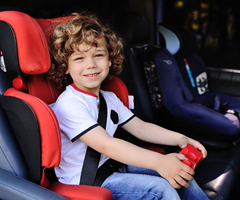 a young boy with curly hair in a booster seat in the back of the car